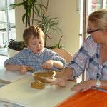 Dieser Junge fertigt gemeinsam mit seiner Mutter einen Aschenbecher für den Papa
