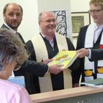 Die beiden Geistlichen übergaben Rolf Müßig ein Kreuz mit einem Regenbogen als Zeichen des Lebens und Brücke zu Gott