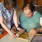 Der Ton wird mittels eines Nudelholzes gleichmaßig dick ausgewalzt für eine Wandtafel