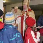 Gemeinsam mit dem Weihnachtsengel verteilt der Nikolaus Geschenke an die Kinder