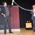 Ein Zuschauer versucht vergeblich die beiden Seile auf gleiche Länge zu bekommen
