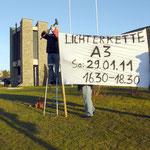 Herr Eras und Herr Karl stellen das Banner auf. Die Vorsitzende des BV überwacht die Arbeit der Beiden