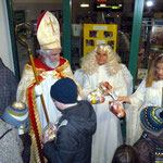 Der Nikalaus verteilt an die Kinder Geschenke; der Engel und die Lichtermaid helfen ihm dabei