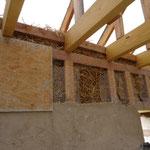 Le haut des murs est assemblé avec des bottes désassemblées. Les galettes de baille sont empilées à la verticale.