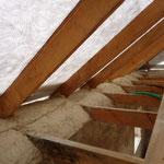 La maçonnerie vient noyer le bas de la charpente et la paille, en affleurant la sous-toiture afin qu'aucune intrusion ne puisse survenir jusqu'à la paille. Les fissures vont être bouchées à la barbotine de chaux.
