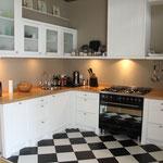 Door stefig op maat gemaakte keuken met massief eiken aanrechtblad en wit gespoten paneeldeuren. Gemonteerd in Ridderkerk.