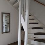 Door stefig op maat gemaakte trapkast met strakke deuren. Voorzien van legplanken en stootborden. Gemonteerd in Maasland.