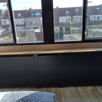 Door stefig op maat gemaakte radiator ombouw met plankenpatroon en eiken vensterbank. Het midden is voorzien van lades.. Gemonteerd in Gouda.