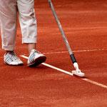 Die Linien des Tennisplatzes werden nachgezogen. Foto: Tobias Bunners