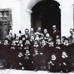 """1957(12 marzo,festa del """"Risparmio""""nell'atrio di Pal.Bianchi gli alunni della 3°elem)Da sx,prof.R.De Vinvenzo e G.Spezzano,il resp.dell'esat.P.Servidio, il direttore V.Minisci,il diret.Cassa Risp.V.Misasci e il prof.Mario Iudicissa(foto di G.Iudicissa)"""