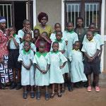 Schüler und Schülerinnen der Taub-Blinden-Schule mit Lehrerin Sarah in der mitte und Lehrerin Rose Rechts. In rotem Oberteil Erzieherin Kevina