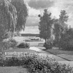 """zurück zum """"Rosengarten"""": 1928 von dem berühmten Lübecker Gartenarchitekten Harry Maasz angelegter rosenbewachsener Zugang zum See; am Eingang erinnert eine Bronzefigur an den Märchenerzähler Wilhelm Wisser"""