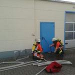 AGT-Trupp während der Türöffnung mit Bandschlinge und Feuerwehraxt