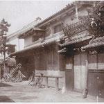 豊村酒造の前には、馬や牛をつなぐための柵があり、人力車や車力(大八車)も見える。壁のコテ絵の周囲の墨もはっきりしている。横の荒神様も祀られておらず、隣の上妻染色店(現在の「藍の家」)の軒には、防火板が下がっている。