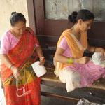 Die Damen nähen die Päckchen in Baumwolle ein