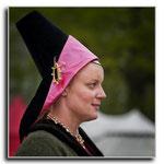 Robe en laine verte et hennin tronqué et bande en velours noir avec revers en soie rose (enluminure de référence sous peu...). Bijoux: Philippe de Rocher.