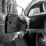 Portière ouverte, assise dans sa voiture, Cécile Aubry change de chaussures sur le trottoir