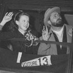 """Cécile Aubry et Pierre Brasseur font signe d'au revoir aux photographes à la gare de l'Est de Paris le 16 février 1951. Ils partent par le Alberg-Express en Allemagne dans la Forêt Noire et en Autriche pour tourner """"Barbe-Bleue""""."""