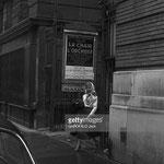 """Cécile Aubry sort du théâtre et passe devant une affiche de la pièce """"La Chair de l'Orchidée"""" collée sur le mur du théâtre"""
