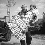 """Le réalisateur Edgar Neville porte Cécile Aubry dans ses bras lors d'une pause sur le tournage de """"La ironia del dinero"""" © pinterest"""