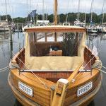 Einer unserer Nachbarn mit seinem selbstgebauten Boot aus Holz. An Bord - eine Tomatenpflanze