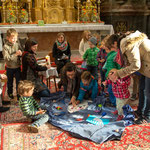 Die Kinder helfen die Glitzerschuppen aufzulegen.