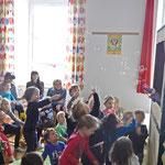 Kinder versuchen die Seifenblasen einzufangen.