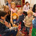 Lotta und Fipsi teilen den Kindern ein Marienbild und Herzkekse aus.