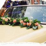 Romantische rozenguirlande op motorkap, met bijpassende versiering op de deurgrepen.