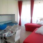 dużego pomieszczenia - salonu z kuchnią wraz z trzema łóżkami