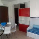 einem großen Kuechen/Wohnraumbereich mit zwei Betten