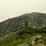 am Rücken sind zwei Wanderer zu beobachten