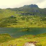 eine kleine Insel im See und darüber thront die Ignaz-Mattis-Hütte