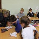 учитель помогает ученикам сделать вертушки