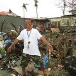 ein fröhlicher Filipino vor seinem völlig zerstörten Haus