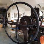 ein gewaltiges Handrad an einer Steindruckpesse