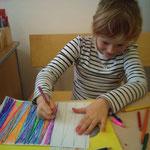 ein Kind beim Malen der Perlen