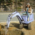 山口さんがユンボで穴を掘っています
