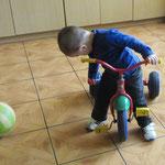 Der Junge freut sich über das mitgebrachte Dreirad