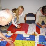 Gäste und GastgeberInnen unterschreiben alle Puzzleteile.