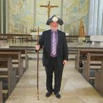 Pfarrer Glaser mit dem Pilgerstab und Pilgerhut, die der Weihbischof in seiner Predigt nutzte
