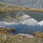 Südwand des Rheinwaldhorns spiegelt sich im Laghetto dei Corti