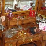 Frasco de cristal rosado de Phil Grenyer: Glasscraft; barra de labios de Marini; monóculo, borche y peina de Lourdes Areal: LXL; juego de tocador plateado de Viti López: el Rastrillo de Viti;