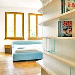 Privatwohnung: Blick ins Schlafzimmer mit raumhohem Regal