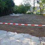 Die bestehenden Natursteinplatten sind frisch verlegt und der Rasen angesät.