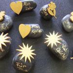 Steine beschriftet und mit vergoldeten Holzteilchen beklebt