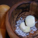 Knoblauch mit grobem Salz in dem Mörser kleinklopfen, damit dem Knoblauch seine typische Strenge entzogen wird und dabei süßlicher schmeckt.