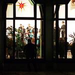 Blick von außen durch die Fenster in den beleuchteten Saal