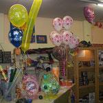 Viele verschiedene Arten von Geschenkpräsentationen. Zu sehen sind: Verpackungsballons, Heliumballons, Gewichtballons unbd ganz hinten ein singender Folienballon.