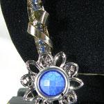 Piuma argentata avvolta da una lamina e conclusa da una corolla che racchiude una pietra marmorizzata azzurra